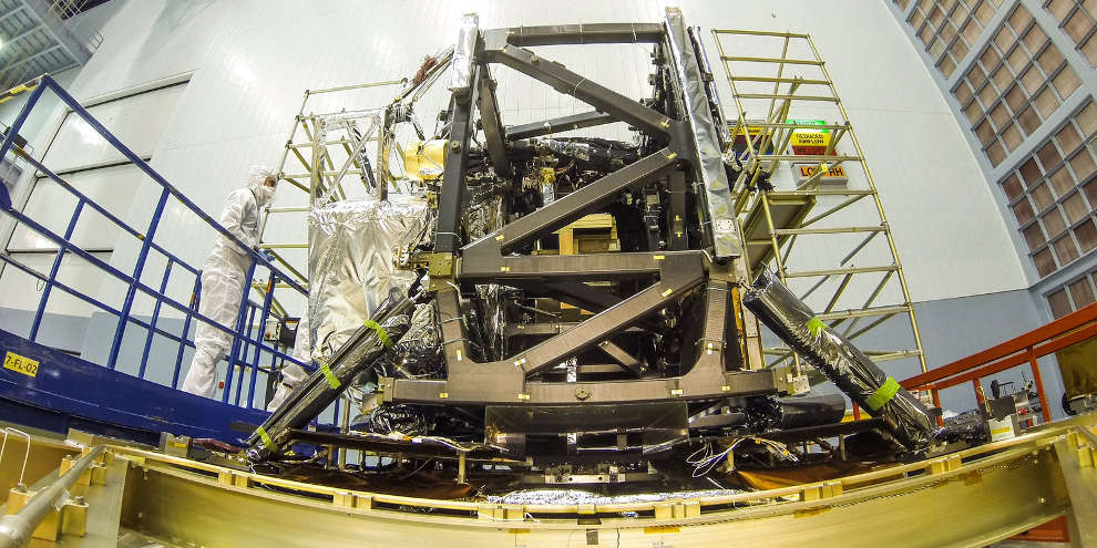 The James Webb Space Telescope's Integrated Science Instrument Module (ISIM) mounted on a test frame. The gold-colored instrument, partly visible inside the frame, is the Canadian-provided FGS/NIRISS (Fine Guidance Sensor/Near Infrared Imager and Slitless Spectrograph)
