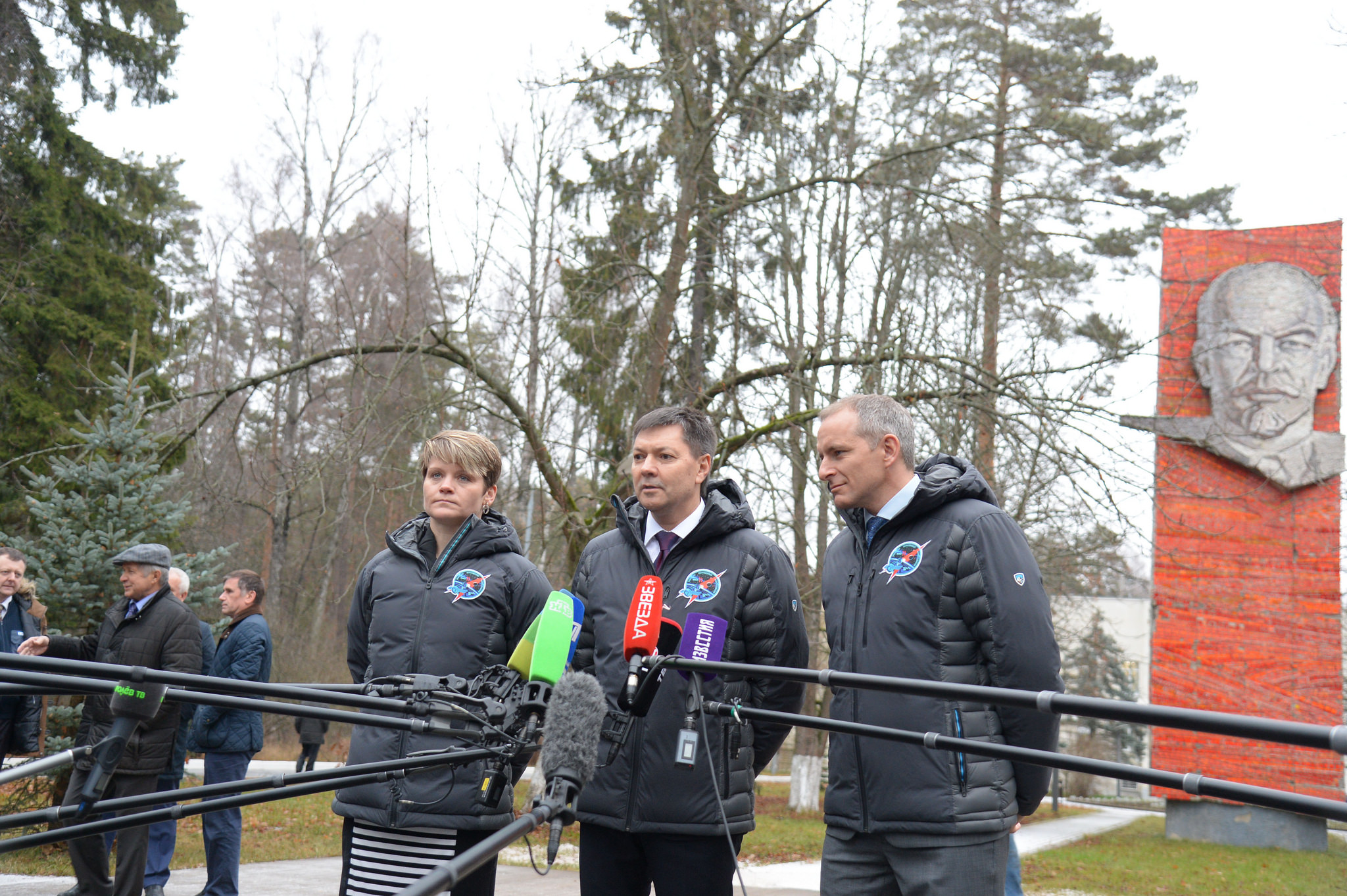 With the statue of Vladimir Lenin serving as a backdrop, Expedition 58 crew members Anne McClain of NASA (left), Oleg Kononenko of Roscosmos (center) and David Saint-Jacques of the Canadian Space Agency (right) answer reporters' questions Nov. 19 at the Gagarin Cosmonaut Training Center in Star City, Russia before boarding a plane to fly to their launch site in Baikonur, Kazakhstan. McClain, Kononenko and Saint-Jacques will launch Dec. 3 on the Soyuz MS-11 spacecraft from the Baikonur Cosmodrome in Kazakhstan for a six-and-a-half month mission on the International Space Station