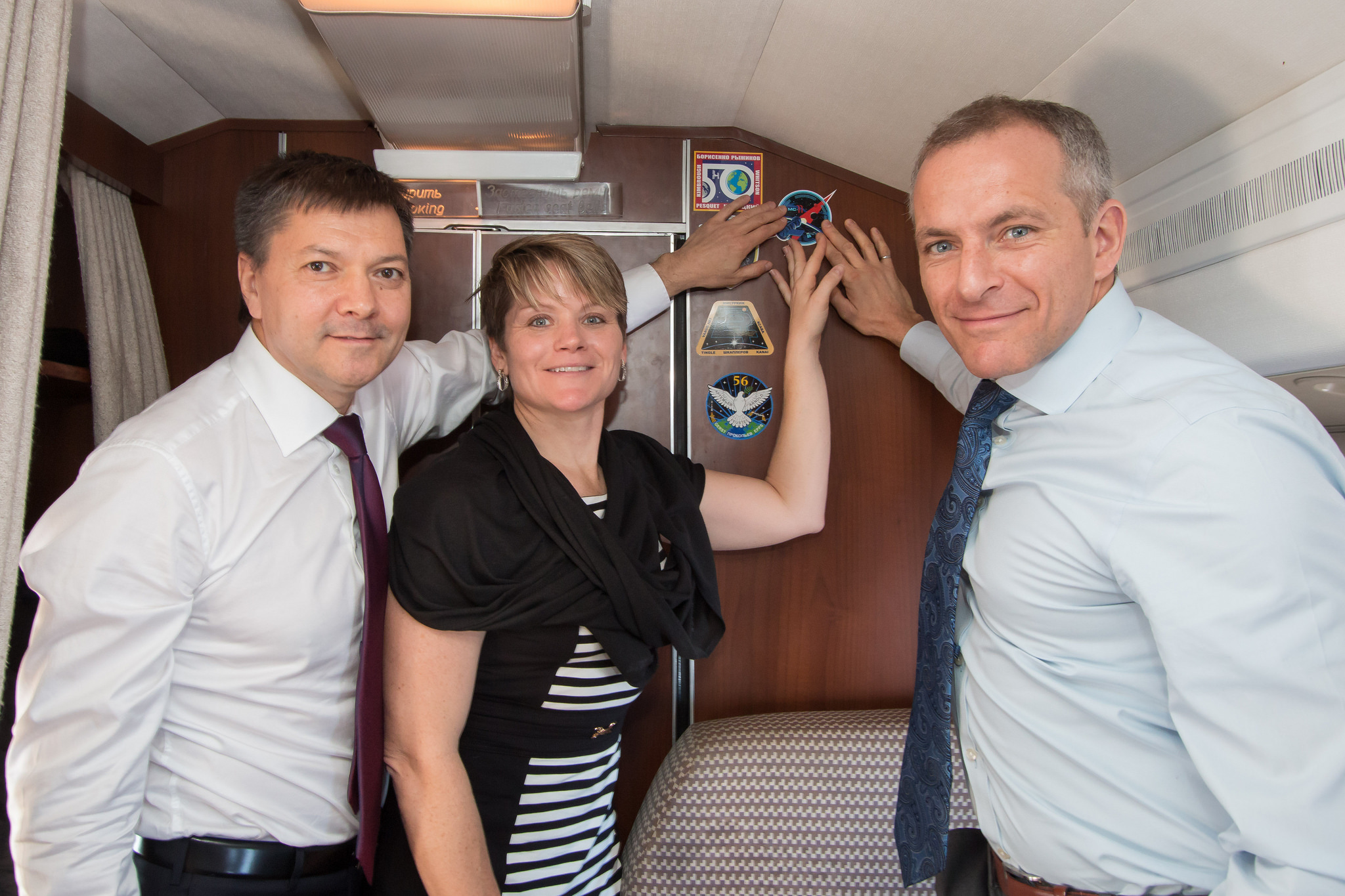 Aboard a Gagarin Cosmonaut Training Center aircraft, Expedition 58 crew members Oleg Kononenko of Roscosmos (left), Anne McClain of NASA (center) and David Saint-Jacques of the Canadian Space Agency (right) affix a Soyuz MS-11 sticker to the wall of the cabin Nov. 19 in a traditional ceremony as they flew to their launch site in Baikonur, Kazakhstan. They will launch Dec. 3 on the Soyuz MS-11 spacecraft from the Baikonur Cosmodrome in Kazakhstan for a six-and-a-half month mission on the International Space Station