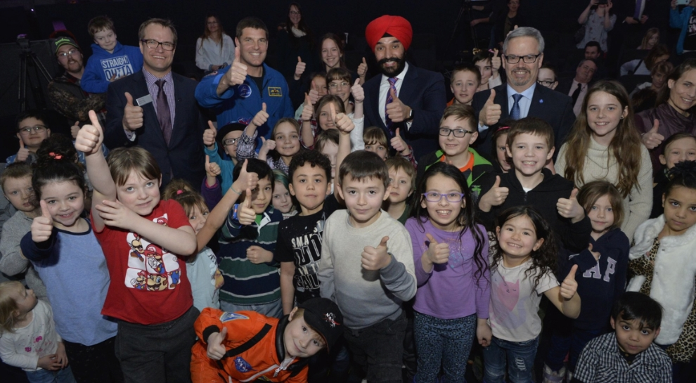 Students pose with (left to right) Alan Nursall, President and CEO, TELUS World of Science, astronaut Jeremy Hansen, ISED Minister Bains, and Canadian Space Agency president Sylvain Laporte